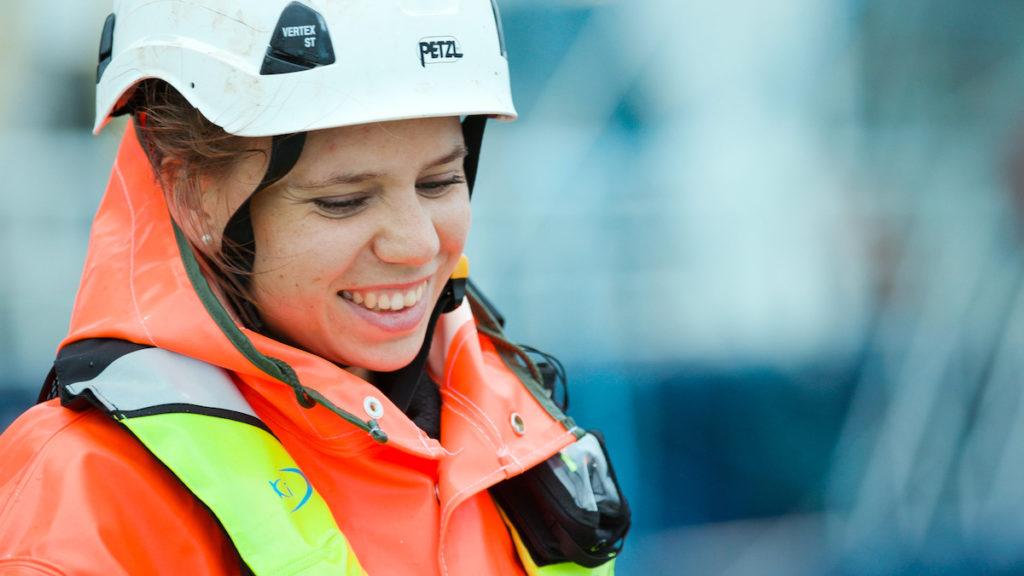 Smilende kvinnelig veterinær på feltarbeid