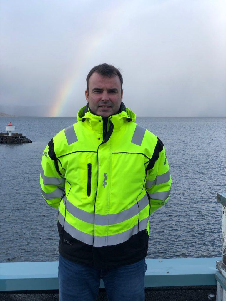 Mann i gul arbeidsjakke foran et hav med regnbue og et fyr