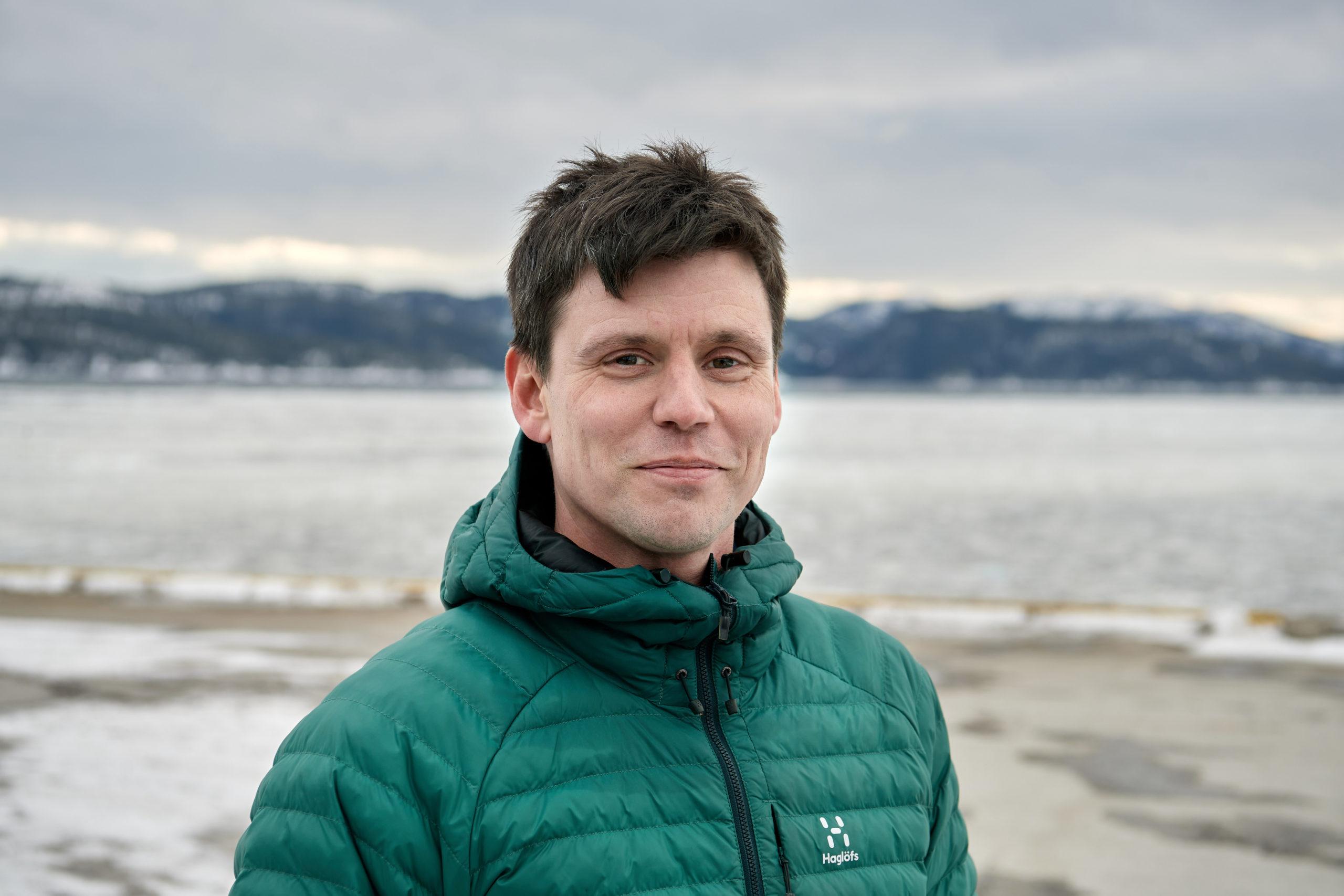 Mann i grønn jakke foran en islagt fjord
